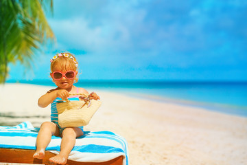 cute little girl with bag relax on tropical beach