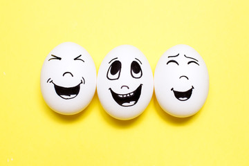 Three eggs with drawn laughing cartoon faces. Friends concept