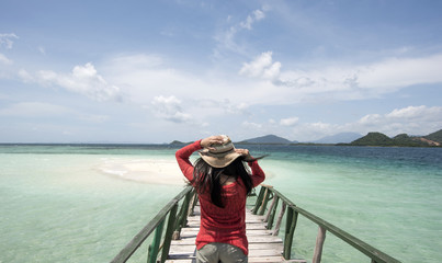 Young Woman Holding Hat at Beach