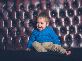 Cute little boy sitting on sofa