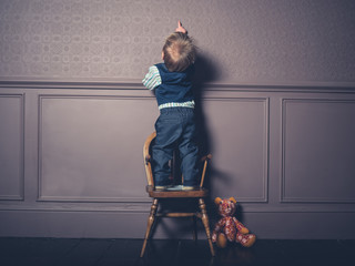 Boy in suit standing on chair