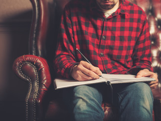 Young man on sofa writing in notebook