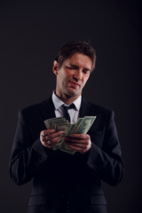 Picture of banker in suit counting dollars