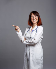 Photo of smiling brunette doctor in white coat and with phonendoscope in glasses points finger at empty space