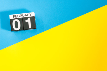 February 1st. Day 1 of february month, calendar on blue and yellow background flat lay, top view. Winter time. Empty space for text