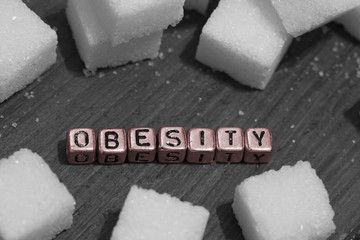 Sugar cubes with the word obesity on beads