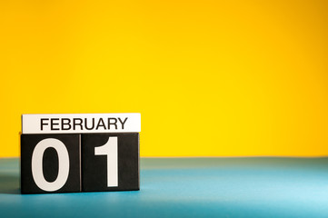 February 1st. Day 1 of february month, calendar on yellow background. Winter time. Empty space for text