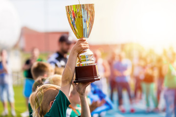 Young Athlete Holding Trophy. Youth Sport Soccer Team with Trophy. Boys Celebrating Sports Achievement. Winning Team of Sport Tournament for Kids. Children Celebrating Soccer Football Championship