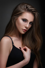 Beauty portrait of a chic woman with long straight hair isolated on a dark gray background.
