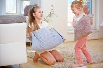 Zwei Kinder machen Kissenschlacht zu Hause