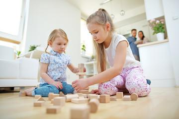 Zwei Mädchen bauen Turm aus Bauklötzen