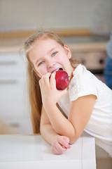 Kind beißt in einen roten Apfel
