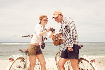 Happy couple with old fashioned bicycles looks at the pictures on the beach.