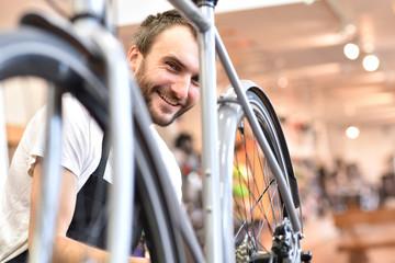 junger sympathischer Fahrradmechaniker repariert Bike im Radladen // young likeable bicycle mechanic repairs bike in a bike shop