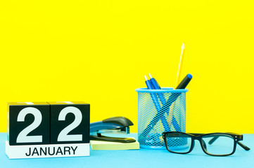 January 22nd. Day 22 of january month, calendar on yellow background with office supplies. Winter time