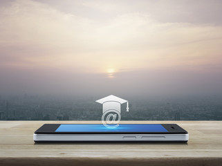 e-learning icon on modern smart phone screen on wooden table over city tower at sunset, vintage style, Study online concept
