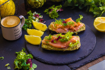 morning breakfast with hot coffee and a sandwich with avocado, soft cheese, lemon and red fish trout on a dark background