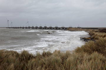 Dunes, wild sea with storm high waves and storm barrier closed