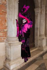 Female Venetian Mask - Cat mask in pink / black elegant costume on St. Mark's Square in Venice with traditional venetian pillar - Venice Carnival