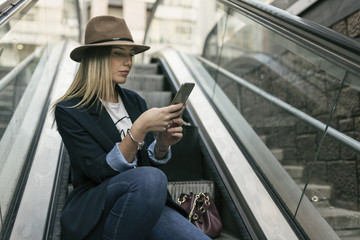 Woman with her smartphone in stairs looking apps and making selfies after shopping