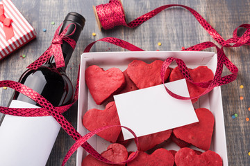 Valentine's Day Background, paper on wooden table. Red velvet heart cookies in Gift box. Ribbon and bottle of wine