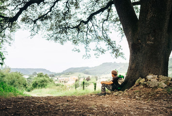 Little backpacker traveler rests under big tree on country road