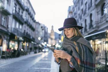 Beauty woman in  the middle of european city in blue hour night city scene looking smartphone