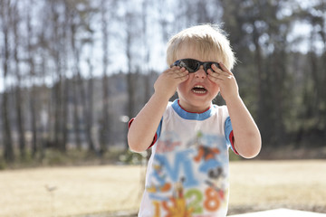 Smiling blonde boy outdoors with sunglasses