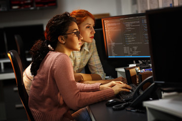 Two female programmers working on new project.They working late at night at the office.