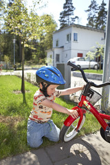 Boy with bicycle in front yard