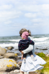 Mother walking on sea coast and carrying baby