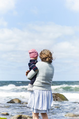 Rear view of mother standing and holding baby against sea