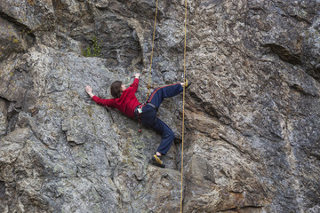 Mountain climber hanging against rock
