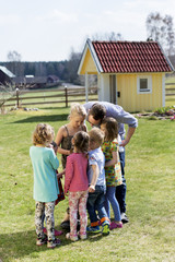 Man standing with group of children on grass on sunny day
