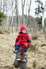 Smiling baby boy wearing red warm suit and cap sitting on tree trunk in forest