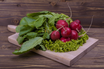bunch of radishes on a wooden board