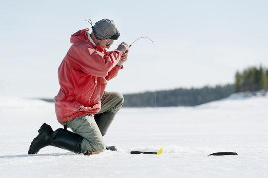 Man ice fishing on sunny winter day