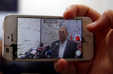 Person uses his mobile phone to shoot a video of Egyptian human rights lawyer and opposition leader Khaled Ali during a news conference about the upcoming 2018 presidential elections, in Cairo
