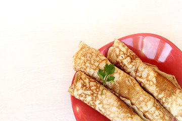 hot dish for reinforcement/ three pancakes wrapped in tubes lie on a red plate top view