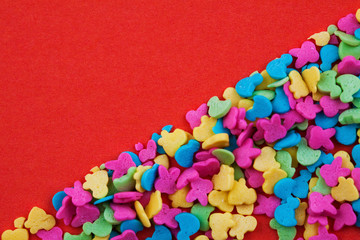 bright multicolored small candy on a red background. Concept for Valentine's Day, Mother's Day. Background for the postcard. Place for text