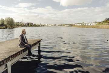 Senior man sitting on jetty at a lake