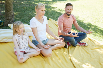 Family with girl practicing yoga on a blanket