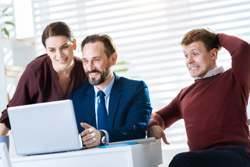 Huge profit. Ambitious pretty three colleagues gazing at the screen while grinning and man touching his head