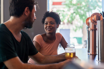 Friends talking and drinking beer at bar
