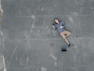 Young businessman with coffee to go lying on tarmac using mini tablet, quadcopter view