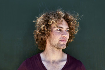 Portrait of smiling young man with curly hair in front of a green wall