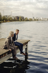 Two businessmen sitting on jetty at a lake