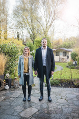 Portrait of smiling couple standing on garden terrace in autumn