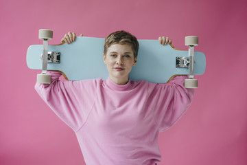 Portrait of woman in pink holding skateboard