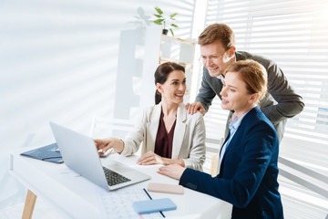 Business opportunities. Glad positive three colleagues laughing while examining report and man holding hands on women shoulders